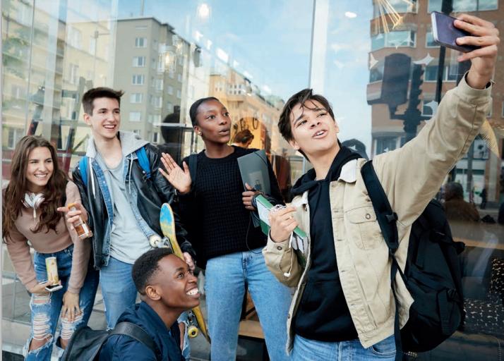 Fem tonåringar poserar framför en mobiltelefon där de tillsammans ska ta en bild.